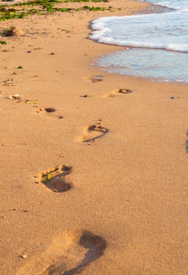 在沙子的脚印靠岸,波浪和脚步 免版税库存照片