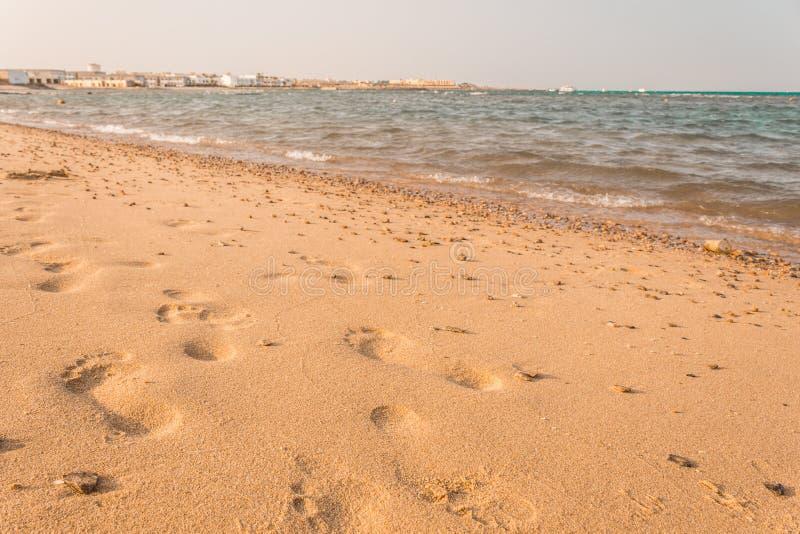 在沙子的脚印 与海波浪的美丽的含沙热带海滩 免版税库存照片