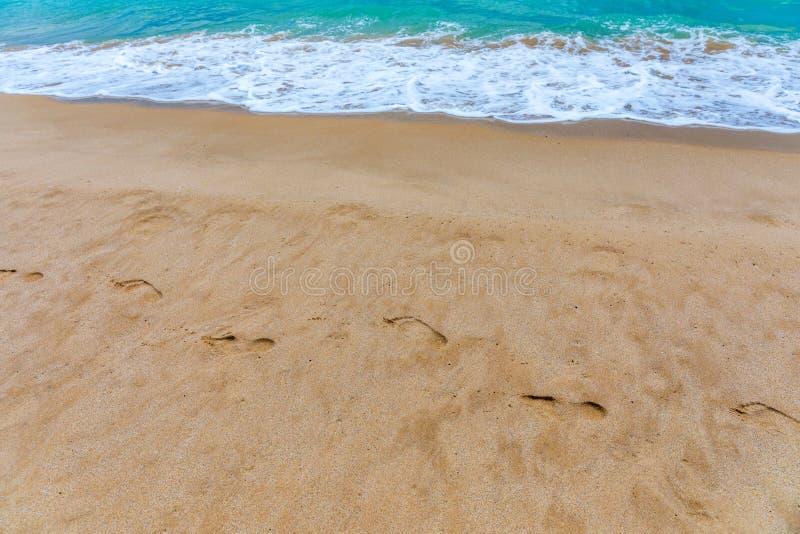 在沙子的脚步 在沙滩的脚印 在沙子的脚印反对海波浪 脚印在一好日子与 免版税库存图片