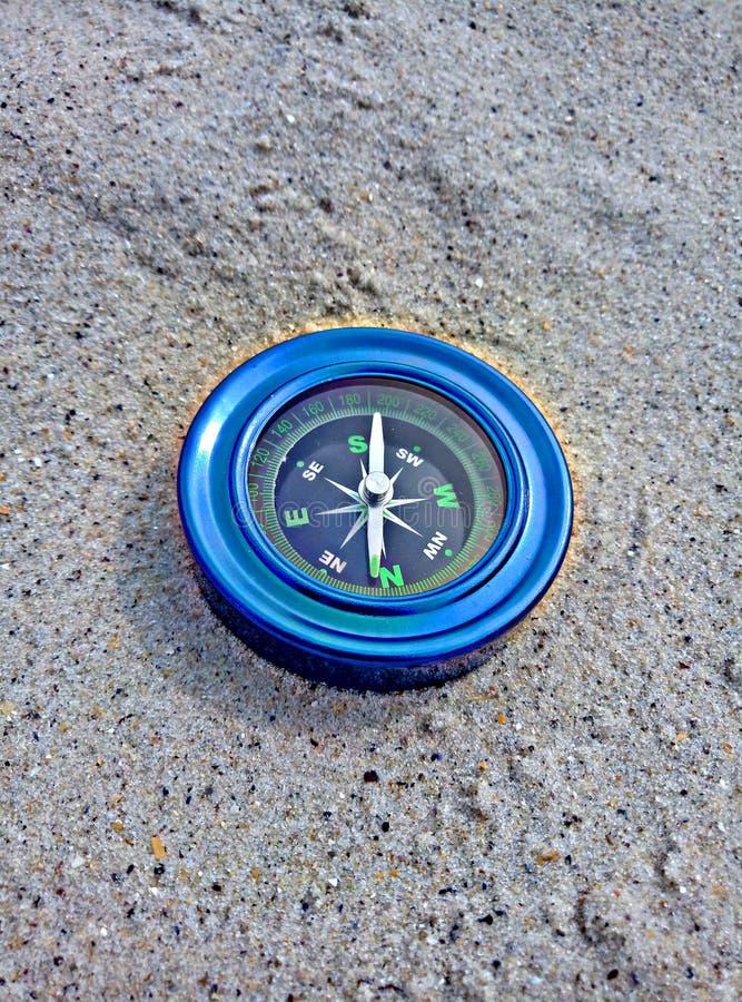 在沙子的蓝色指南针 库存照片