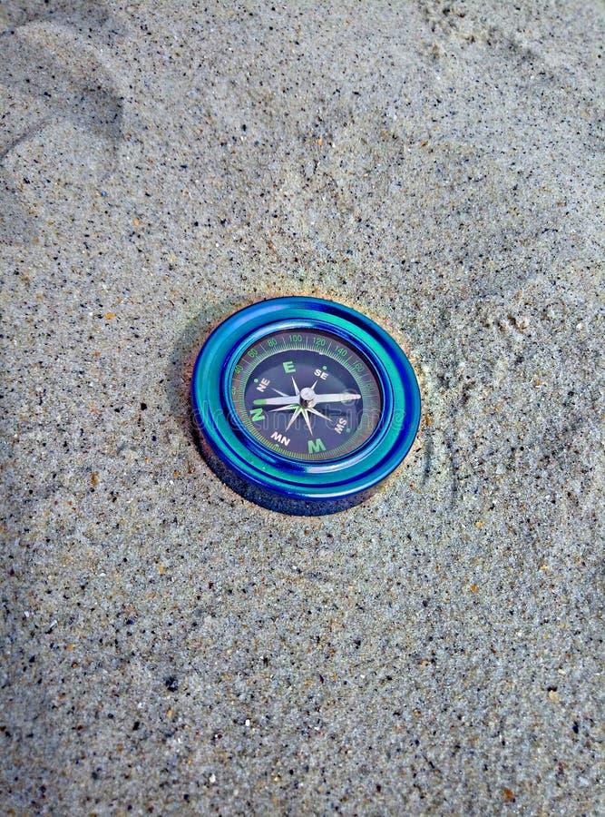 在沙子的蓝色指南针 库存图片