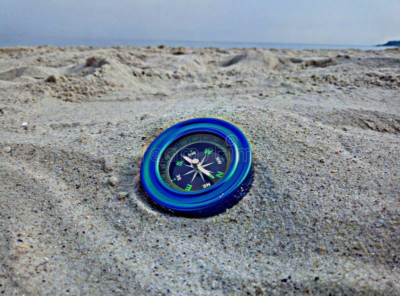 在沙子的蓝色指南针 免版税库存照片