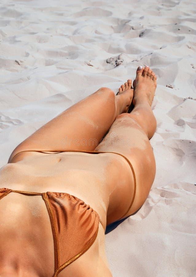 在沙子的被晒黑的女性身体。 免版税图库摄影