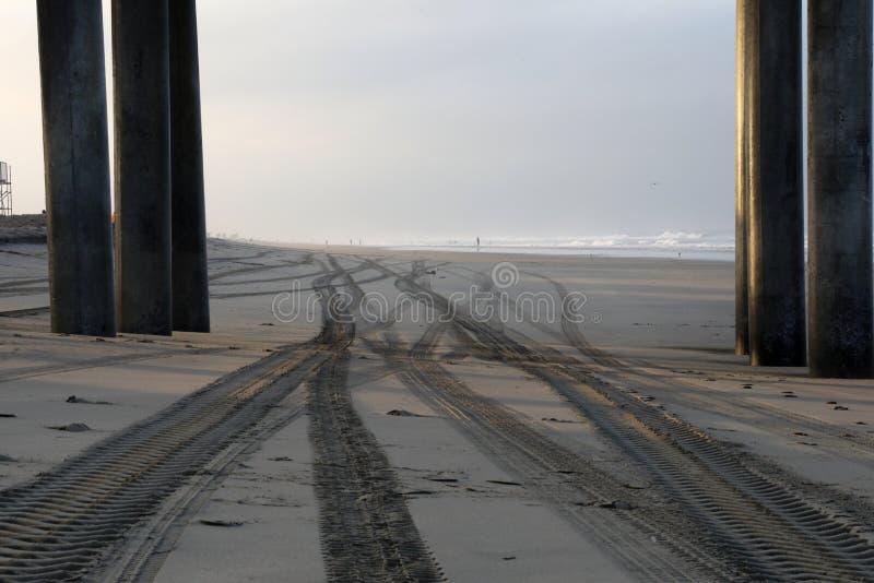 在沙子的轨道在日出在亨廷顿海滩,加利福尼亚 免版税库存照片