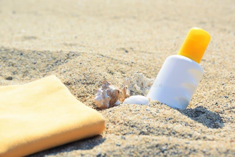 在沙子的遮光剂管在海滩旁边 图库摄影