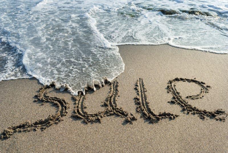 在沙子的题字销售,海浪,海水 免版税库存照片