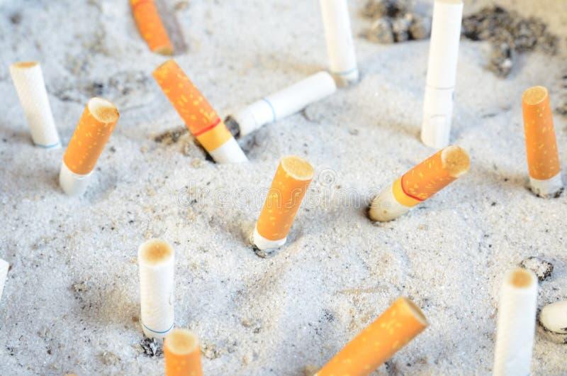 在沙子的香烟残余部分 免版税库存图片