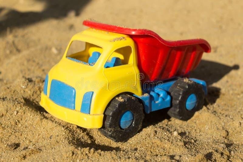 在沙子的黄色红色和蓝色卡车玩具,在海滩 库存照片