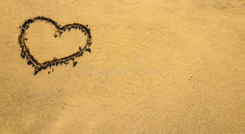 在沙子的晴朗的海爱标志 重点的符号在沙子被画 免版税图库摄影