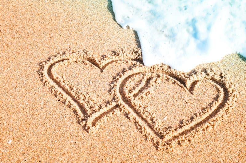 在沙子绘的一个对心脏在夏天在海 库存照片