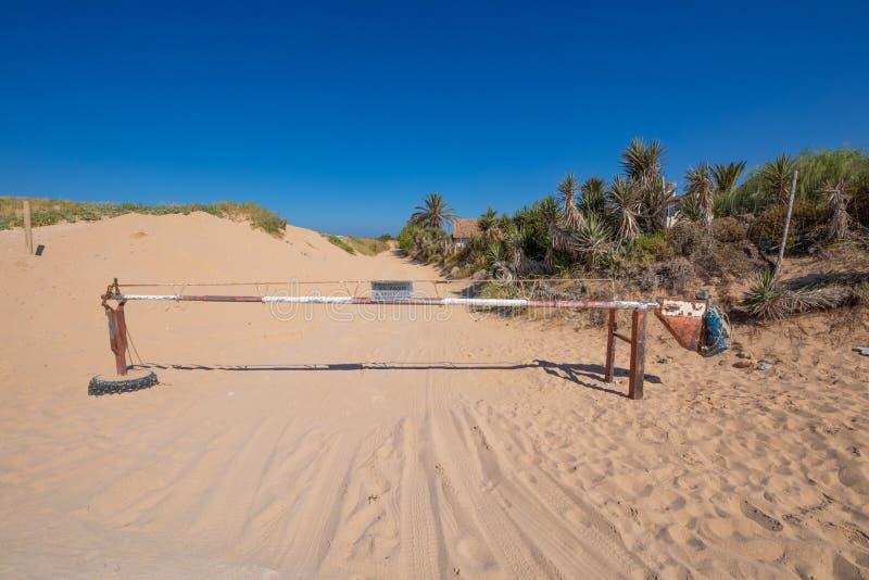 在沙子轨道的白色和红色金属障碍 图库摄影