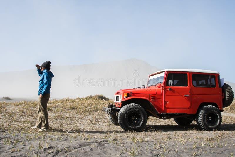 在沙子,供以人员沙丘的游人在沙漠,在Bromo山腾格尔,东爪哇省,印度尼西亚的大草原的公路车辆期间 库存图片
