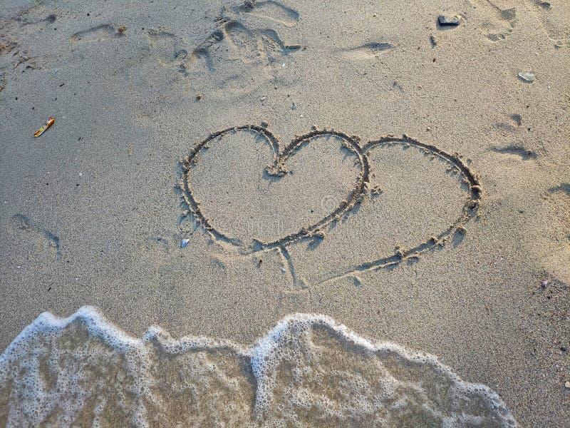 在沙子,有两心脏画 下面泡影波浪来临到一点空间,夏天概念 华伦泰概念 免版税库存图片
