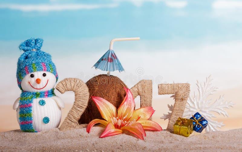 在沙子,雪人,在海洋的背景的圣诞节球的题字2017年 免版税库存照片