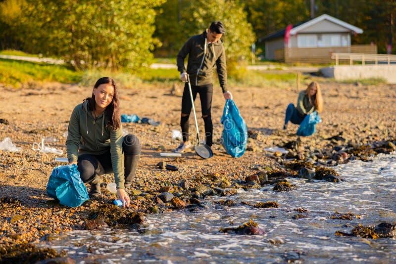 在沙滩上捡垃圾的小队里 库存照片
