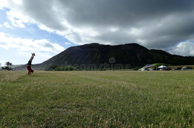 在沙滩公园的Handstanding有Koko头火山口的在背景中 免版税库存图片