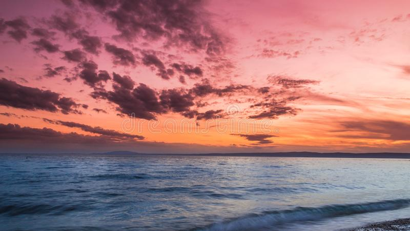 在沙滩的克罗地亚人的日落与令人惊讶的天空 免版税库存图片
