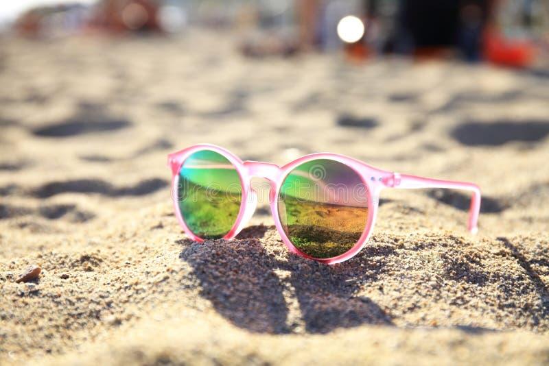 在沙滩的太阳镜在夏天-葡萄酒颜色样式 免版税库存照片