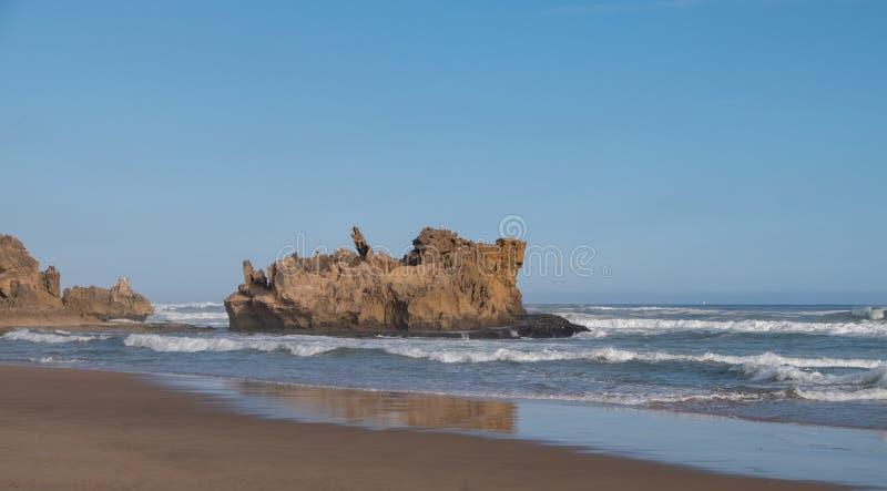 在沙滩的岩石在海,Knysna的布兰顿,被拍摄在日落,南非 免版税图库摄影