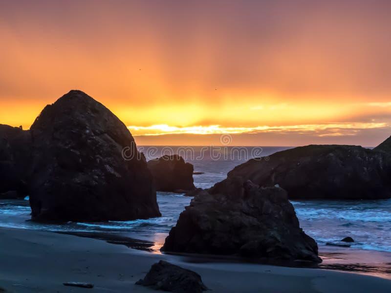 在沙滩的日落与海堆 库存照片
