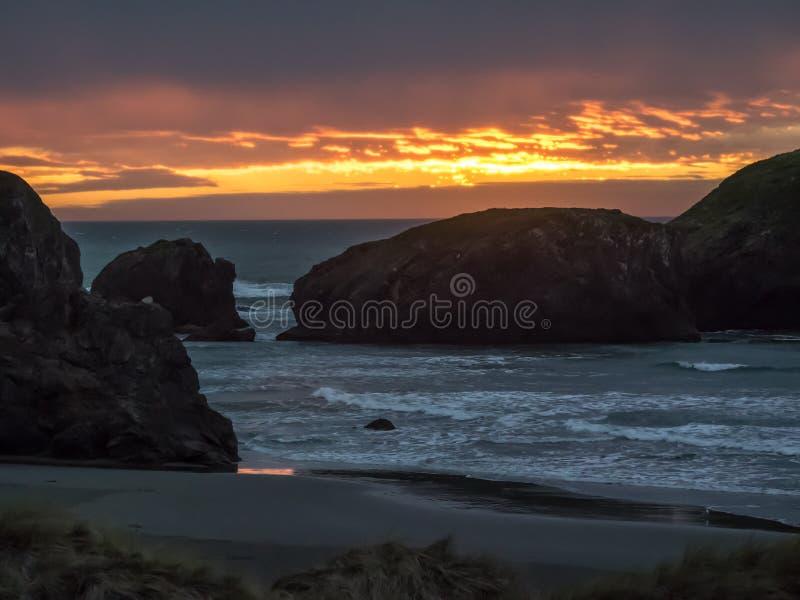 在沙滩的日落与海堆 免版税库存图片