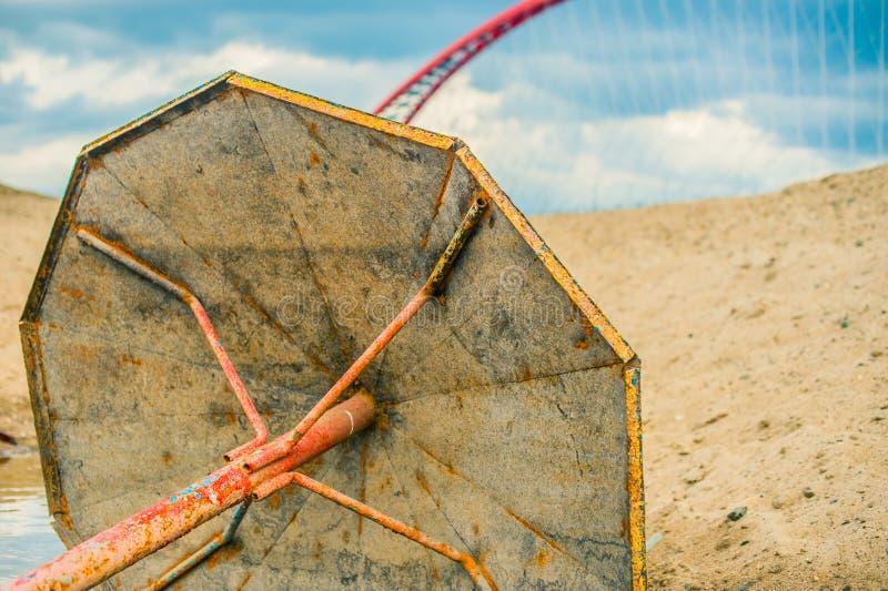 在沙滩的被放弃的生锈的金属遮阳伞,在红色桥梁和蓝天背景  免版税库存照片
