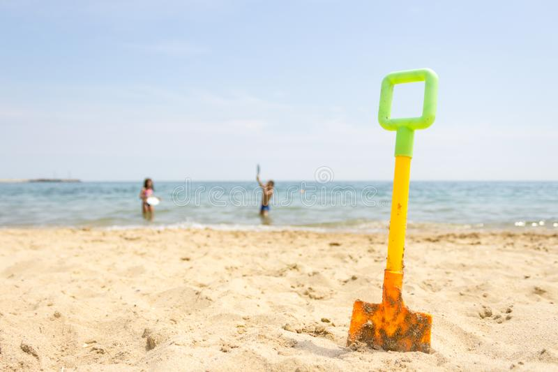 在沙滩的黄色塑料玩具铁锹在使用在海的海边和孩子在背景中 免版税库存图片
