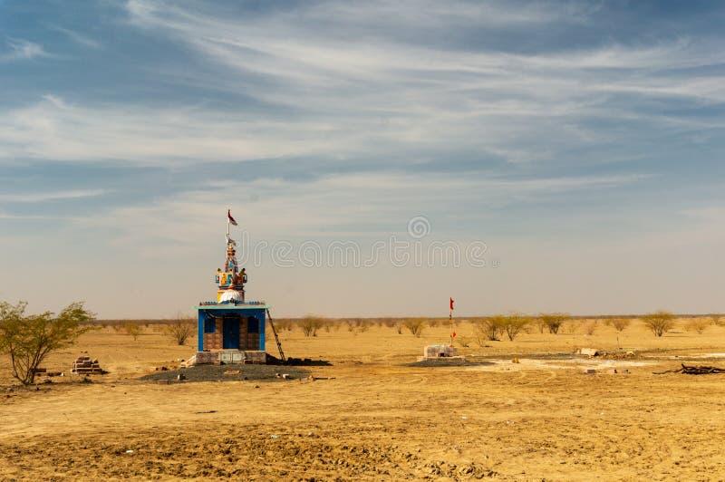 在沙漠中间的小装饰的印度寺庙有多云天空蔚蓝的 免版税库存图片