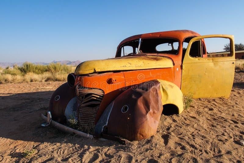 在沙漠围拢的单粒宝石的被击毁的汽车在纳米比亚 免版税库存照片