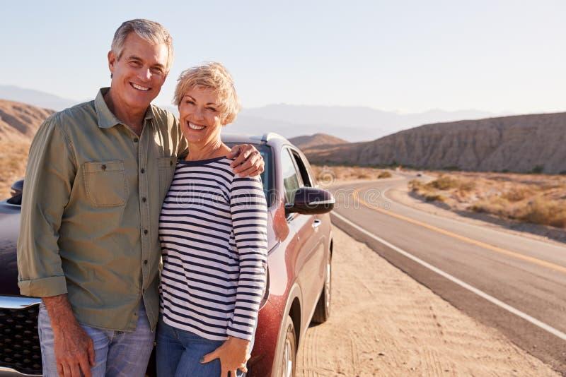在沙漠路旁的资深白色夫妇身分乘汽车 免版税图库摄影
