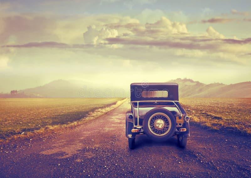 在沙漠路的葡萄酒汽车 免版税库存照片