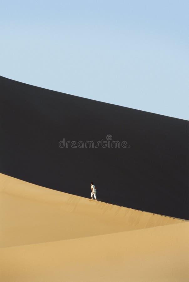 在沙漠间沙丘铺沙走的妇女 免版税库存照片