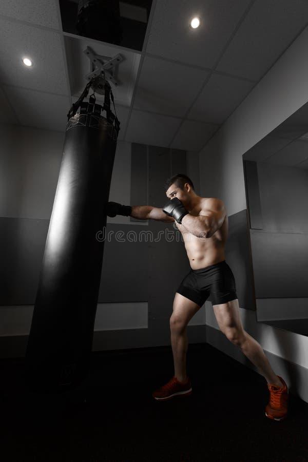 在沙袋的年轻拳击手火车 免版税库存照片