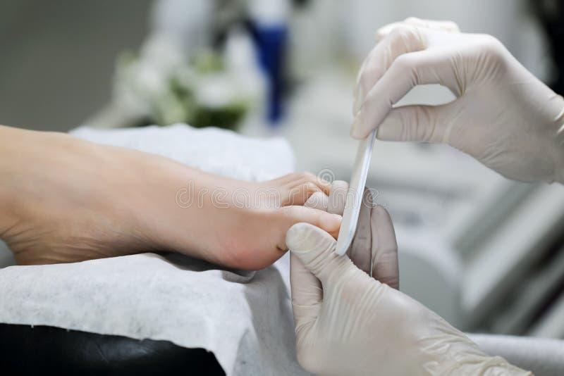 在沙龙的专业砍得恨深的伤口趾甲 免版税库存图片
