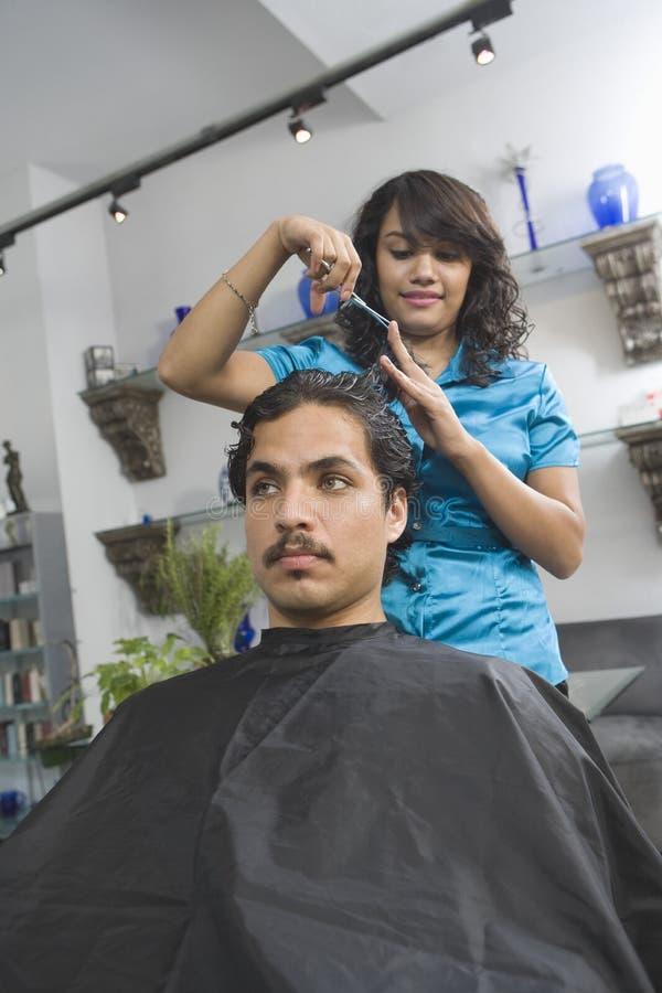 在沙龙的女性美发师切口人的头发 免版税库存照片