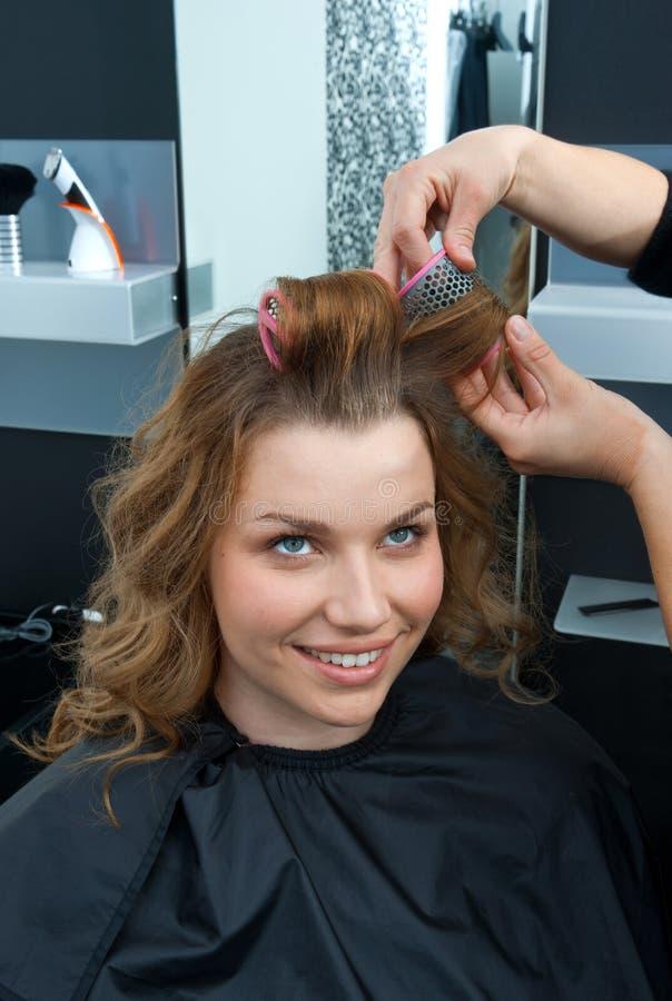 在沙龙的美发师卷曲的妇女头发 库存照片