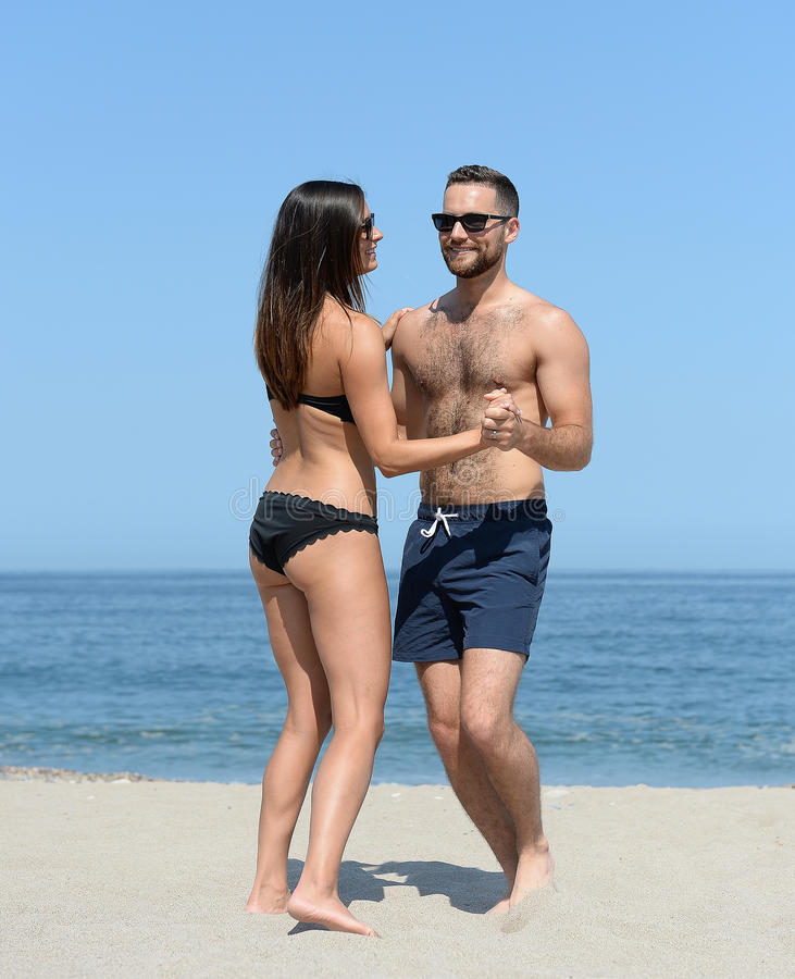 在沙滩的年轻夫妇跳舞 库存照片
