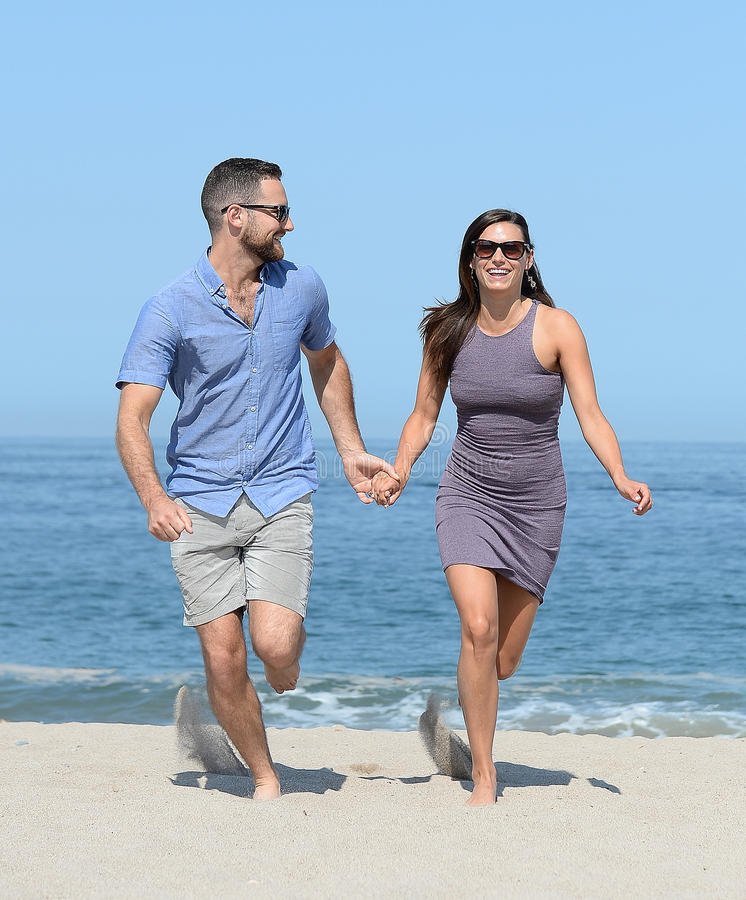 在沙滩的年轻夫妇 免版税库存图片