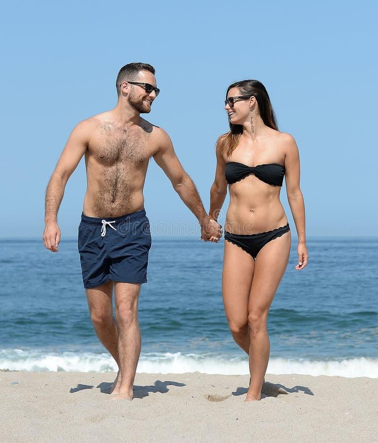 在沙滩的年轻夫妇 免版税库存照片