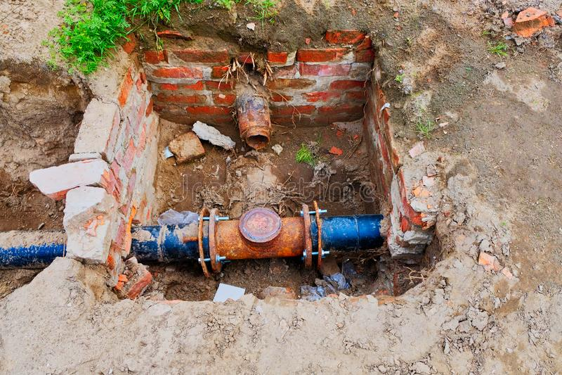 在沟槽的老生锈的污水管子从看法上 库存照片