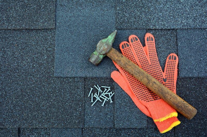 在沥青屋面的看法盖背景 屋顶木瓦-屋顶 沥青屋面盖锤子、手套和钉子 库存图片