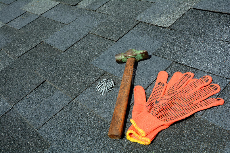 在沥青屋面的看法盖背景 屋顶木瓦-屋顶 沥青屋面盖锤子、手套和钉子 库存照片