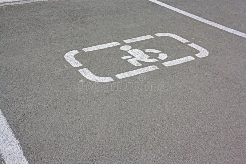 在沥青的残疾停车处标志 有残障的标志停车位 图库摄影