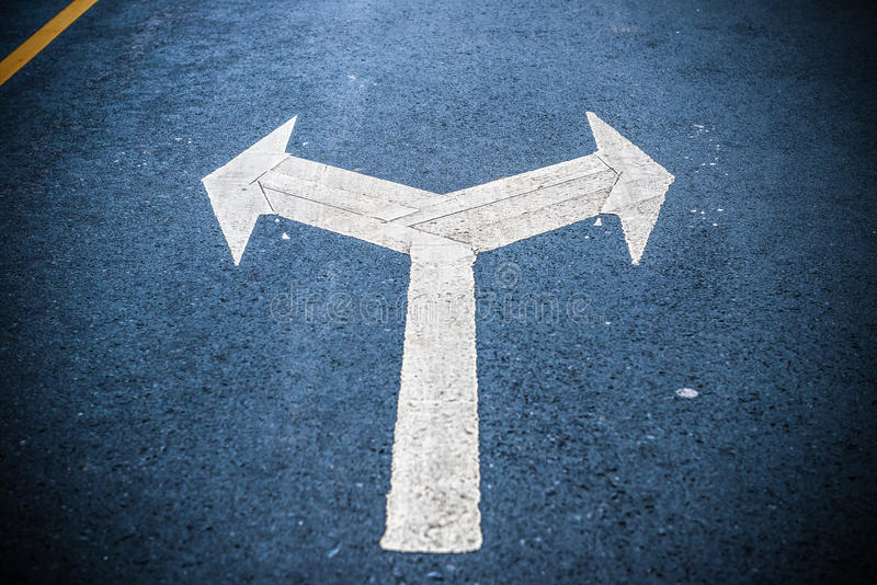 在沥青路的双重旁边白色定向箭头 免版税库存照片