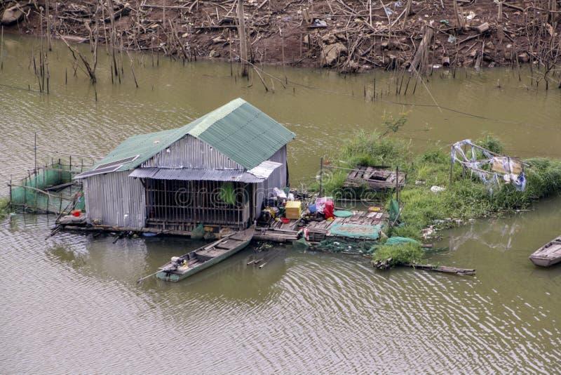 在河中间的议院棚子有小船和庭院的 免版税库存照片