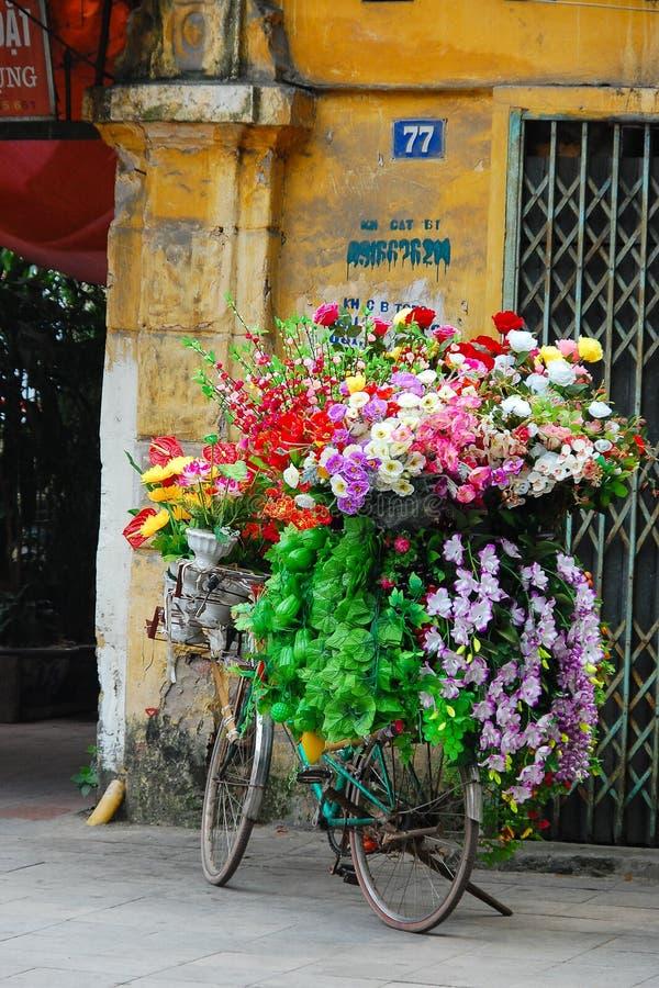 在河内越南骑自行车在街道上的运载的花 图库摄影