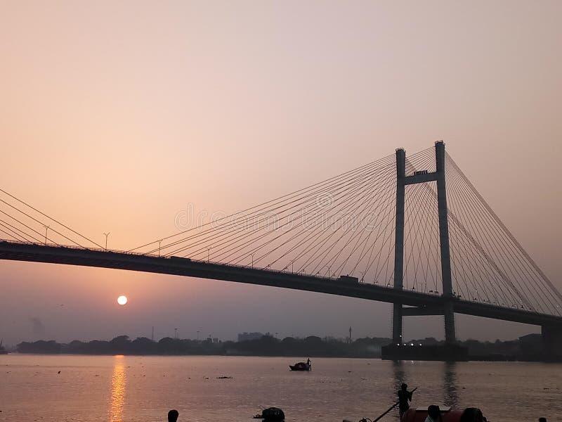 在河和桥梁的日落视图 免版税库存照片