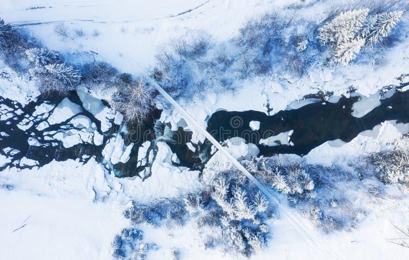 在河和桥梁的鸟瞰图在冬时 从空气的自然冬天风景 在雪a下的森林冬时 免版税图库摄影