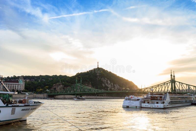 在河和盖勒特小山的游轮在日落在布达佩斯,匈牙利 免版税图库摄影