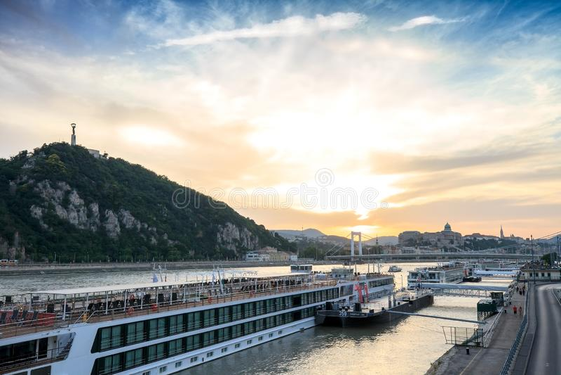 在河和盖勒特小山的游轮在日落在布达佩斯,匈牙利 免版税库存照片
